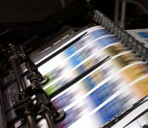 Drukpers met drukwerk dat door de stansmachine schiet.